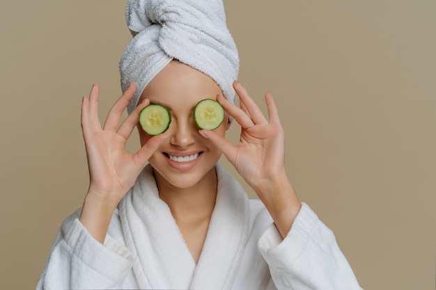 Woman covers eyes with cucumber slices nourishes skin smiles happily