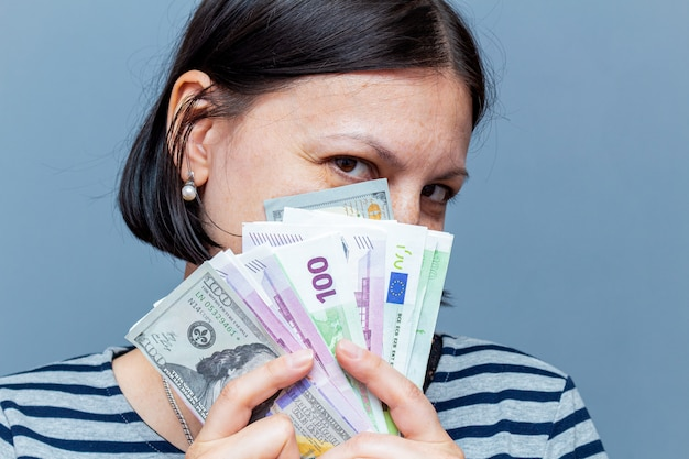 Woman covers face with banknotes on the gray wall
