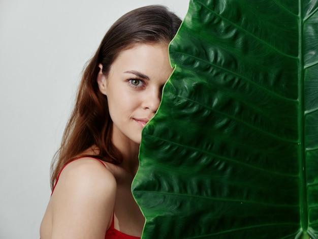 女性は彼女の顔の半分を緑の葉の魅力の明るい背景で覆います