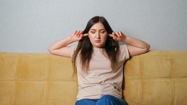 Женщина закрывает уши и ругается на шум соседей, сидя на диване