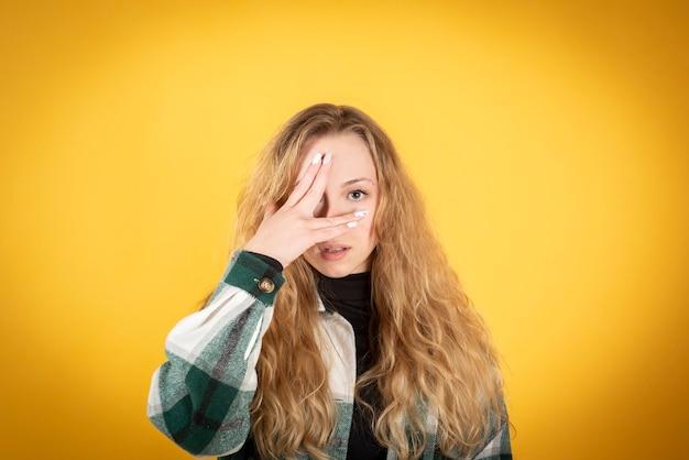 Женщина закрывает глаза рукой на желтом фоне