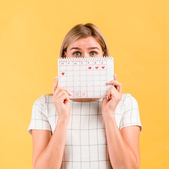 Woman covers her face with period calendar