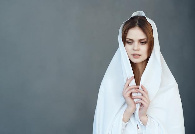 여자는 흰색 천 매력 어두운 배경 포즈로 자신을 다룹니다. 고품질 사진
