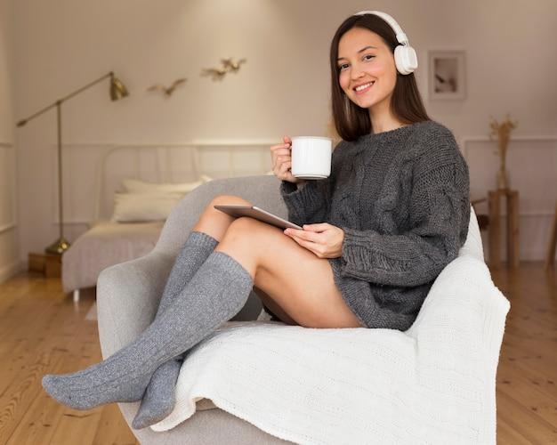 Donna in vestiti accoglienti con la tazza che si siede in poltrona