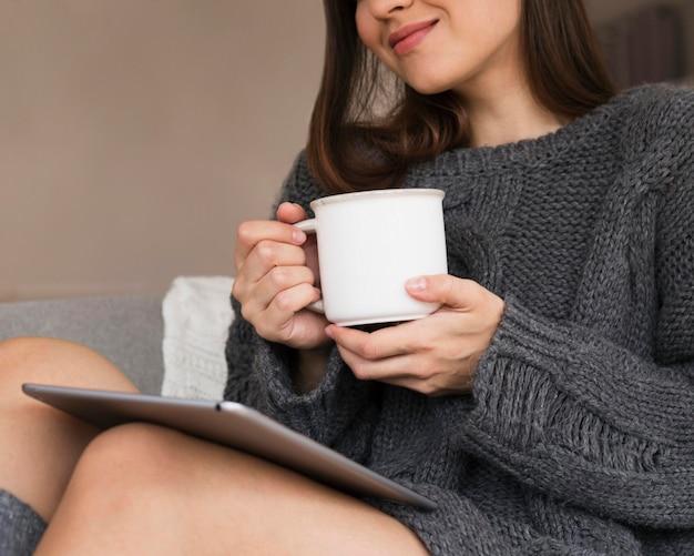 Donna in abiti accoglienti con tazza e tablet