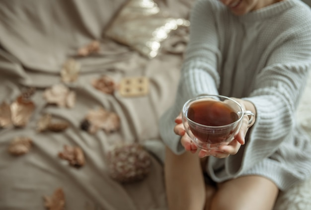 A woman in a cozy knitted sweater holds a cup of tea in her hands, copy space.
