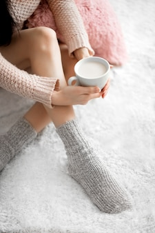 Woman in cozy room with cup of cocoa in her hand.