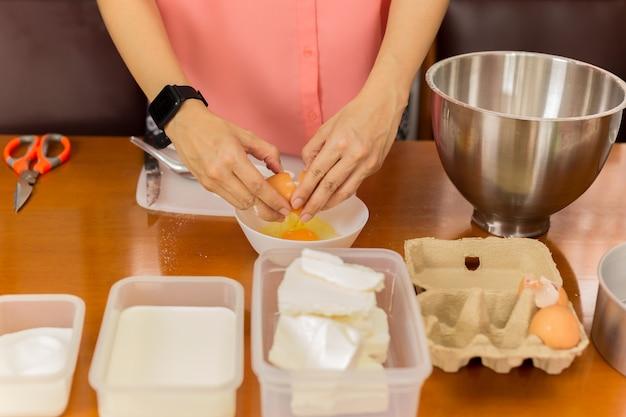 女性は白いボウルに卵を割る
