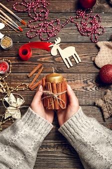 Женщина создает стильные новогодние подарки, украшает свечу корицей
