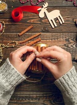 Женщина создает стильные новогодние подарки, украшает свечу