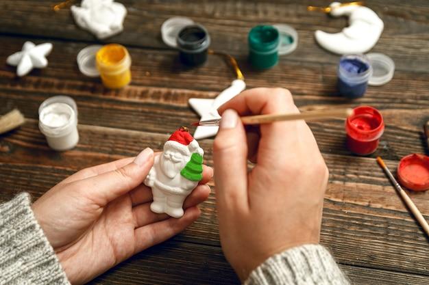 女性はスタイリッシュなクリスマスプレゼントを作成し、磁器の置物をペイントします。