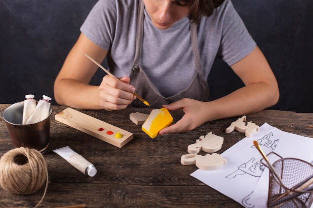 A woman creates a christmas tree toy in her workshop. paints a wooden blank in yellow.