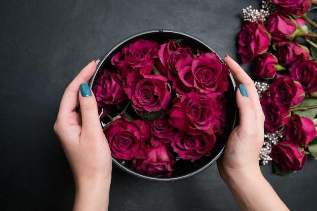 어두운 배경에 상자에 빨간 장미 꽃다발 구성을 만드는 여자. 플로리스트 리와 꽃꽂이의 예술. 아름다운 디자인 컨셉