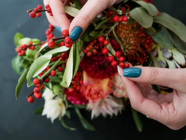 暗い背景に秋の花とベリーの配置を作成する女性。花束のデザインと構図のアート生け花。