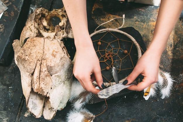 Женщина создает композицию ловец снов на камне