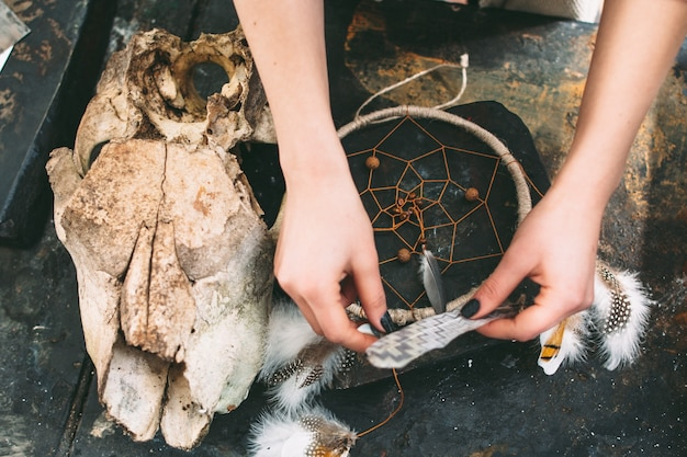 Woman creating dreamcatcher composition on stone