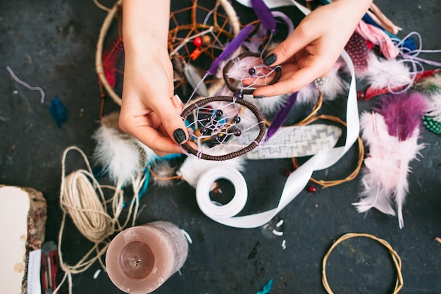 Woman creating dreamcatcher from sewing accessories