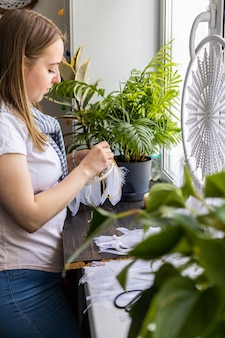 Woman creator making handmade tribal ethnic dreamcatcher enjoying work or hobby at workshop