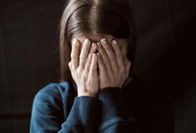 여자는 그녀의 손으로 그녀의 얼굴을 덮고 울으십시오. 가족의 폭력.