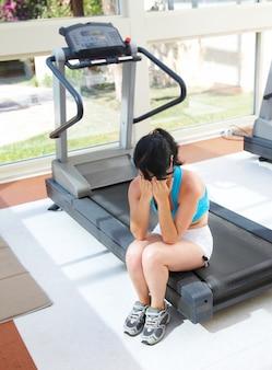 Woman cries at a sports training apparatus.