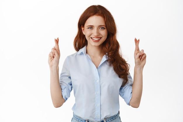 여자는 행운을 위해 손가락을 교차하고, 자신감 있는 표정으로 바라보고, 소원을 빌고, 기도하고, 결과를 기다리고, 흰색 위에 서 있습니다.