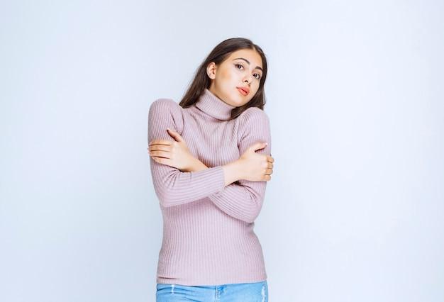 腕を組んで寒さを感じる女性。