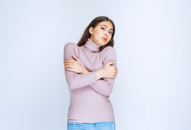 Woman crossing arms and feeling cold.