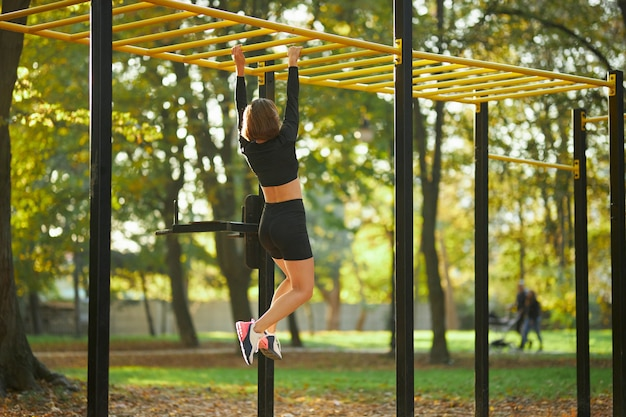 Woman crossing on horizontal bar during outdoors activity