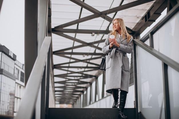 Женщина пересекает мост и пьет кофе