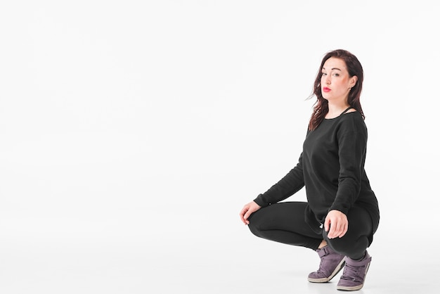 Woman crouching against blank white backdrop