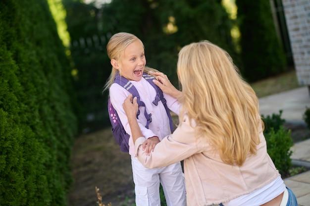 Woman crouching beside an enthusiastic little girl