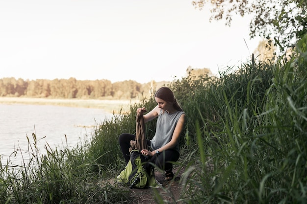 Woman crouching near the lake removing clothes from the backpack
