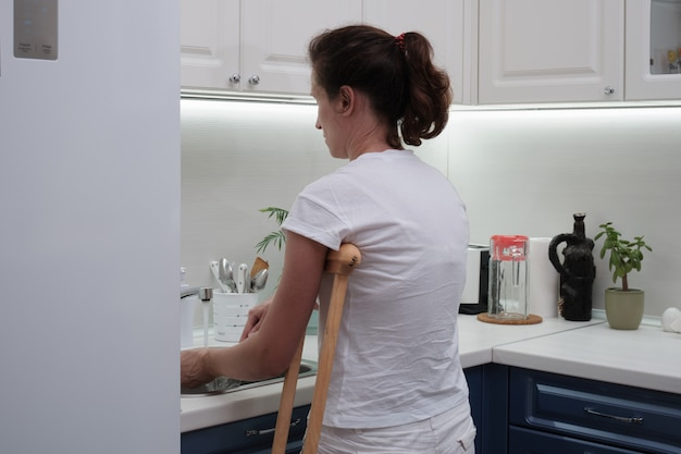 Woman on crutches washes the dishes in the kitchen