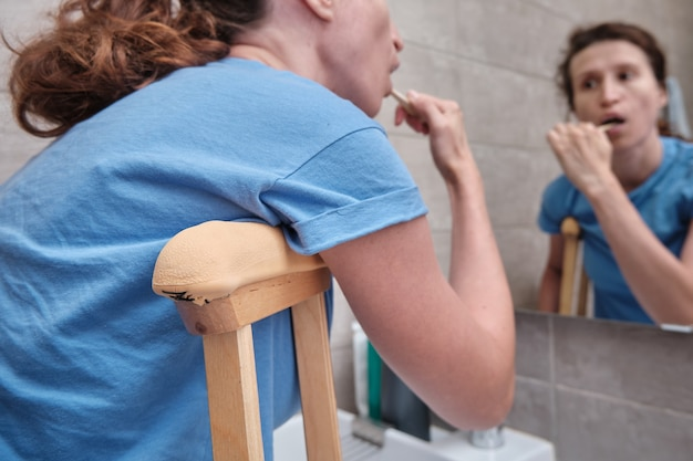 A woman on crutches with a broken leg brushes her teeth in the bathroom