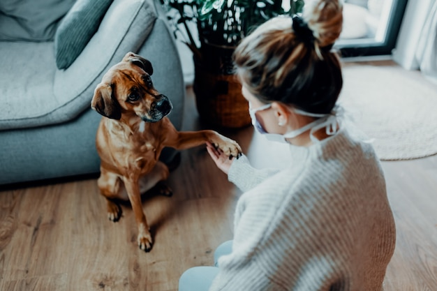 Woman cuddles plays with her dog at home because of the corona virus pandemic covid19