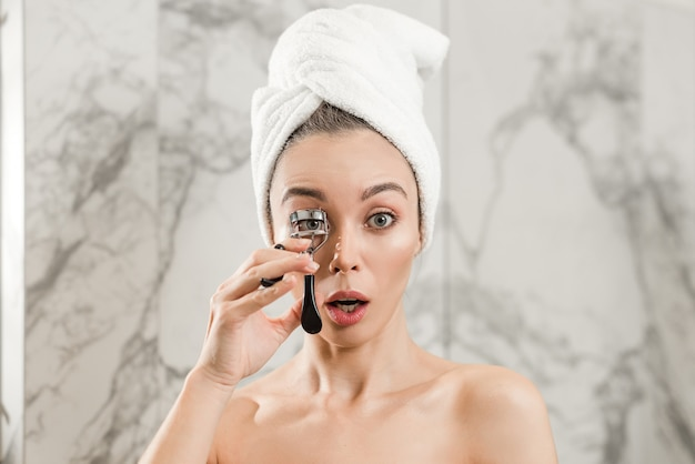 Woman curling eyelashes with curler in bathroom after shower