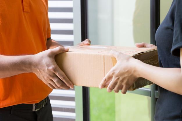 女性客が自宅前の配達員から小包を受け入れて受け取る