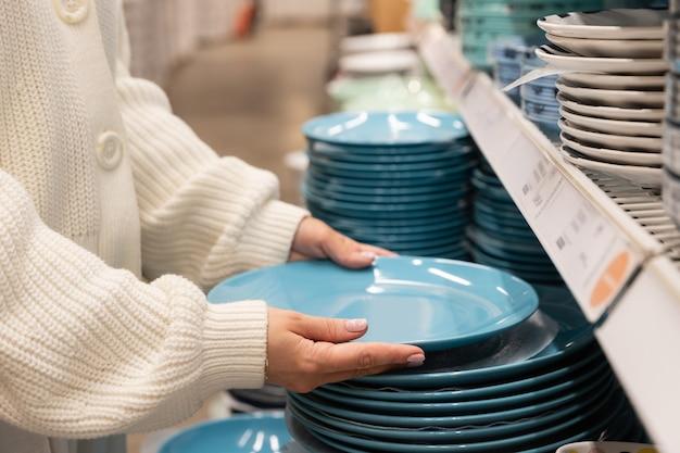 Женщина-клиент выбирает и покупает тарелки из голубой глины