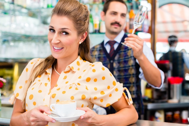 Woman customer in coffee bar drinking cup of cappuccino
