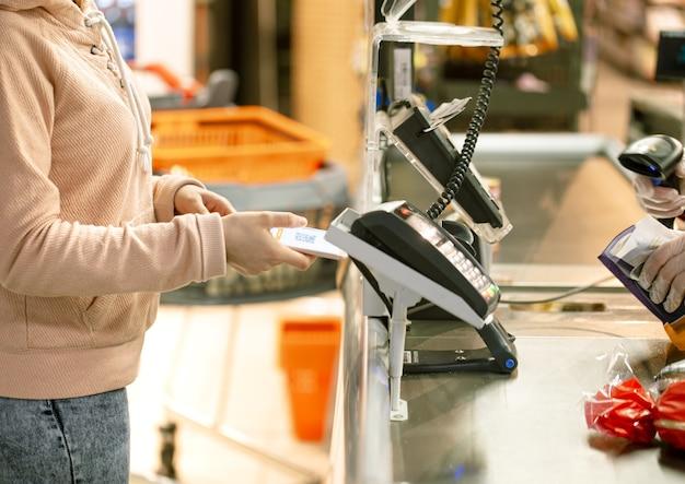 Женщина-клиент, держащая телефон возле терминала, совершает бесконтактные платежи с использованием концепции приложения в магазине, женщина-покупатель платит с мобильного телефона.
