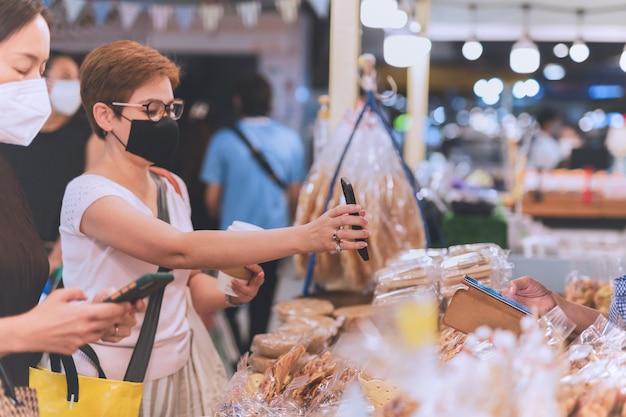 Covid-19 동안 휴대전화로 온라인 결제를 보여주는 보호용 마스크를 쓴 여성 고객.