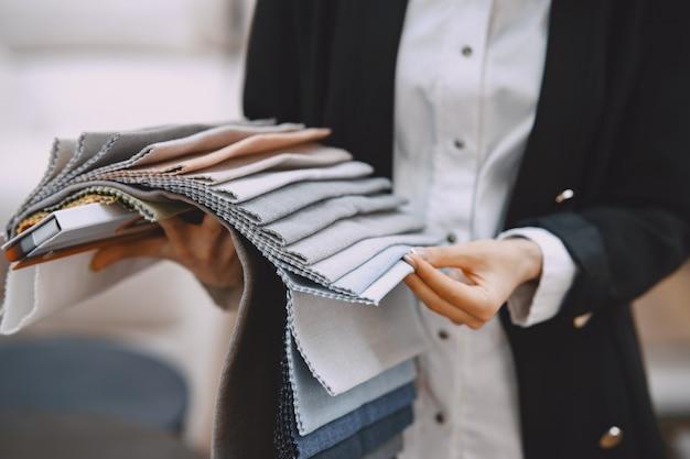 Женщина-клиент ищет красивую ткань в магазине тканей