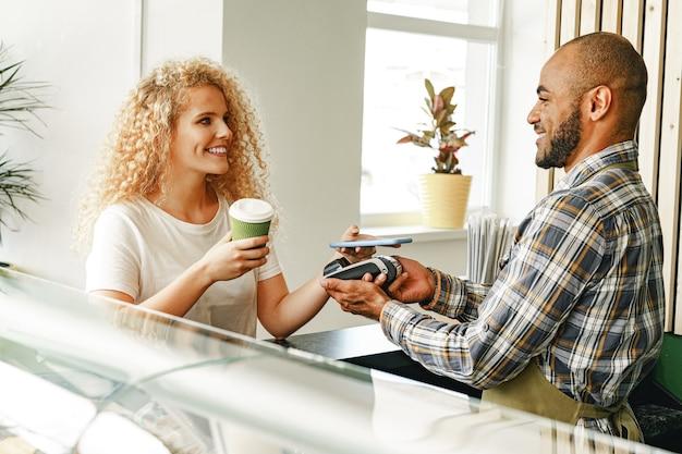 非接触技術を使用して携帯電話でコーヒーを支払う喫茶店の女性顧客