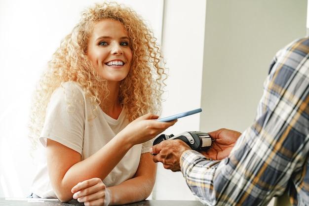 非接触型テクノロジーを使用して携帯電話で支払う女性顧客