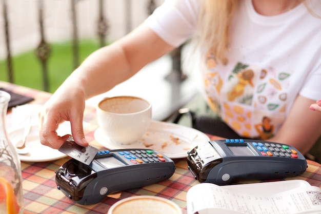 Woman customer paying with credit card at coffee shop
