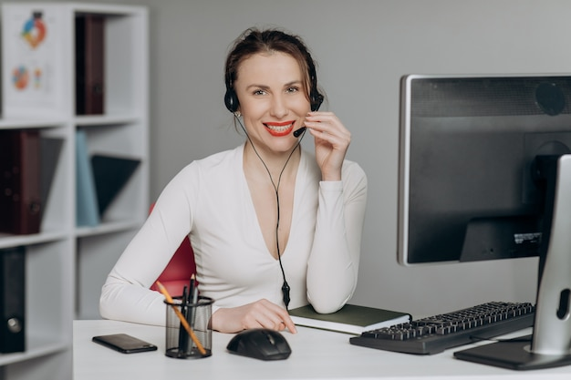 Woman customer support agent receptionist wear headset consult online client.