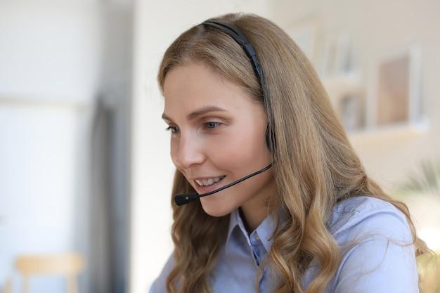 Оператор службы поддержки клиентов женщина с гарнитурой и улыбается.