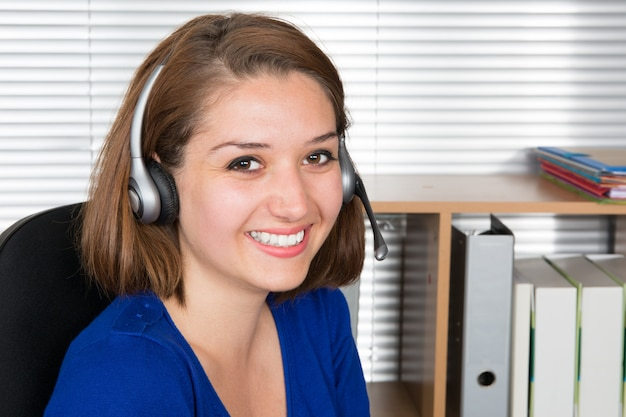 Woman customer support operator with headset and smiling