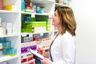 Woman customer with a folder in the pharmacy looking at the medicines on the shelf