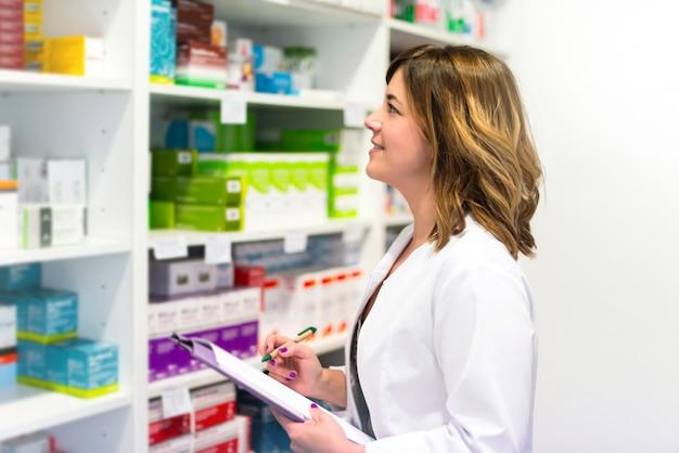 Женщина-клиент с папкой в аптеке, глядя на лекарства на полке